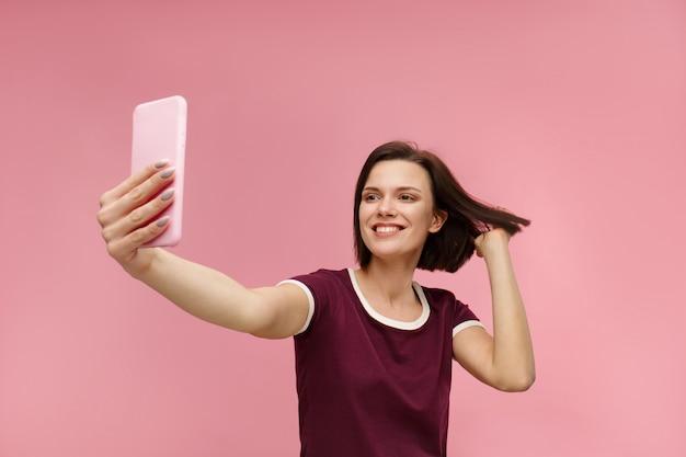 Mulher morena jovem engraçada fazendo selfie