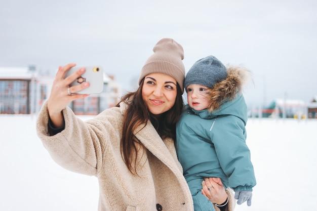 Mulher morena jovem mãe bonita com menino bonito em roupa de inverno fazendo selfie na rua