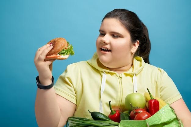 Mulher morena jovem robusta está olhando para o hambúrguer com o mouse aberto, mantendo as frutas e vegetais na mão. conceito de tentação prejudicial à saúde temporal em vez de escolher uma alimentação saudável.