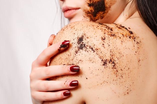 Mulher morena limpa a pele do esfoliante corporal de café na parede branca isolada.