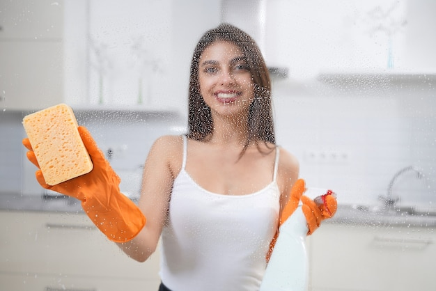 Mulher morena limpando janela com detergente