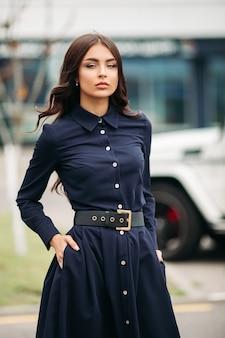 Mulher morena linda e confiante com maquiagem e cabelos ondulados em um vestido azul escuro