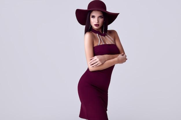 Mulher morena linda elegante em um vestido colorido e um chapéu largo