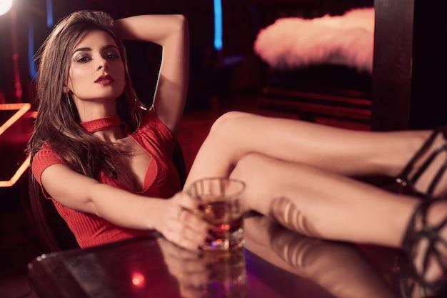 Mulher morena linda em um vestido vermelho com um copo de uísque