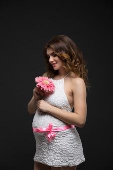 Mulher morena linda grávida em um vestido branco com penteado e maquiagem perfeita, segurando flor rosa