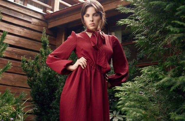 Mulher morena linda moda vestido vermelho no jardim