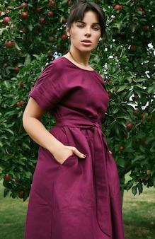 Mulher morena linda no vestido clássico da moda no jardim de maçã