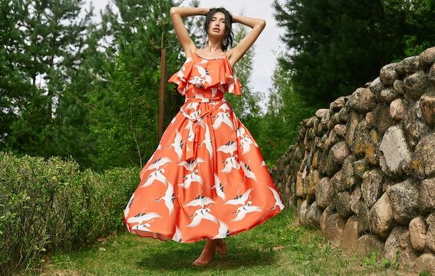 Mulher morena linda no vestido da moda laranja no jardim de maçã