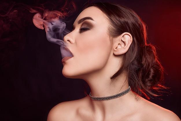 Mulher morena linda sedutora de glamour, fumando cigarro eletrônico