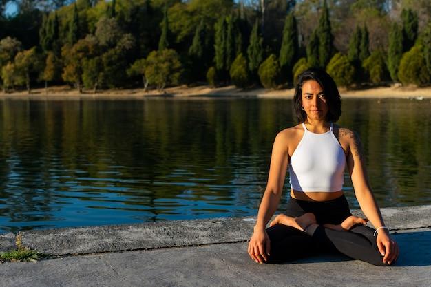 Mulher morena magra sentada em roupas esportivas praticando ioga pela manhã