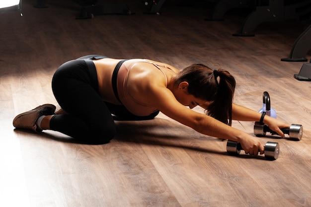 Mulher morena mais modelo de tamanho, fazendo exercícios de alongamento em um ginásio escuro