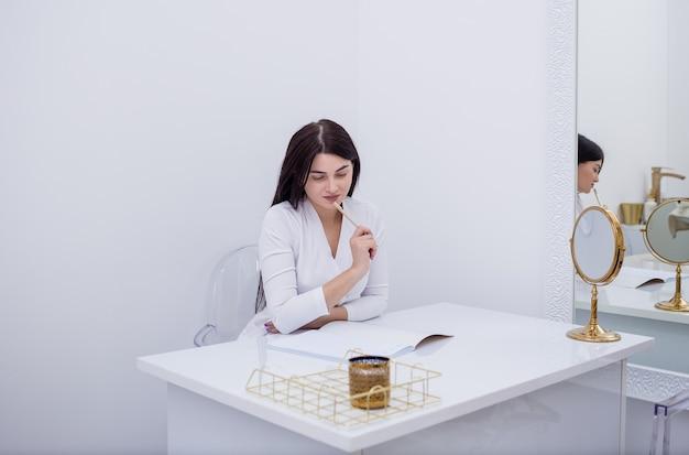 Mulher morena médica está sentada em uma mesa no escritório e fazendo uma anotação