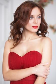 Mulher morena modelo beleza em vestido vermelho. moda luxo maquiagem e penteado, close-up