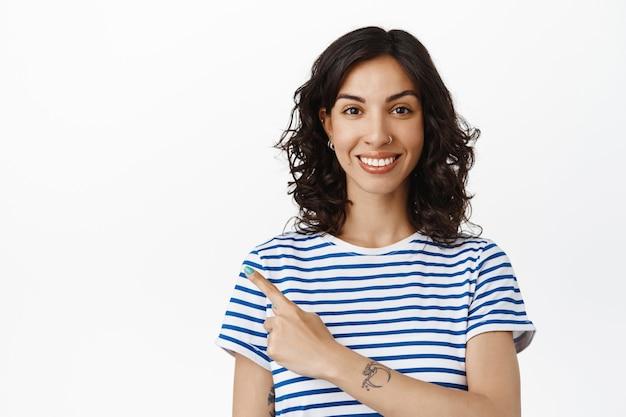 Mulher morena moderna sorridente apontando o dedo no canto superior esquerdo, mostrando um banner de propaganda no espaço da cópia, em uma camiseta listrada em branco