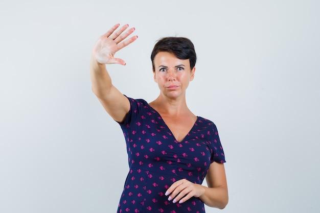 Mulher morena mostrando recusa ou sinal de parada em vestido estampado de roxo e vermelho e olhando sério, vista frontal. Foto gratuita