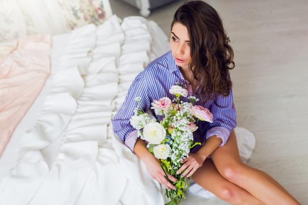 Mulher morena muito alegre com uma camiseta listrada sentada no chão com flores da primavera nas mãos