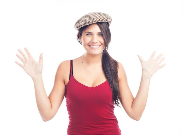 Mulher morena muito sorridente e alegre com tampa francesa e top vermelho