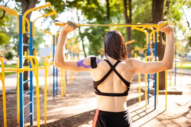 Mulher morena musculosa posando com banda de resistência de fitness no parque