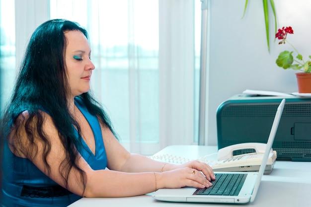 Mulher morena no escritório em casa, trabalhando em um laptop. foto horizontal