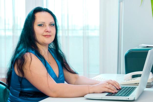 Mulher morena no escritório em casa trabalhando no laptop enquanto olha para a câmera. foto horizontal