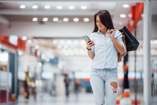 Mulher morena no supermercado com muitos pacotes e telefone nas mãos tem dia de compras.