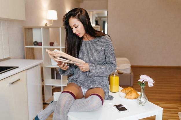 Mulher morena ocupada de suéter cinza e meias até os joelhos lendo jornal e bebendo suco