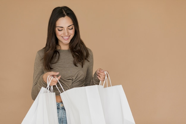 Mulher morena olhando em sacolas de compras