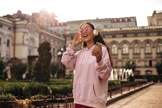 Mulher morena otimista com um capuz elegante e óculos de sol rosa cantando, segurando o telefone e ouvindo música em fones de ouvido do lado de fora