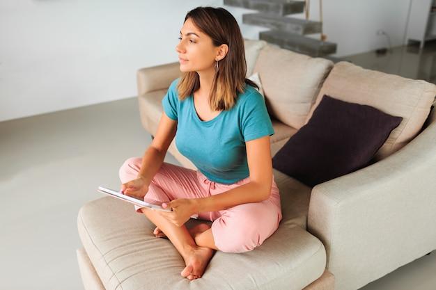 Mulher morena, passar o tempo em casa, usando tablet, assistindo vídeo on-line