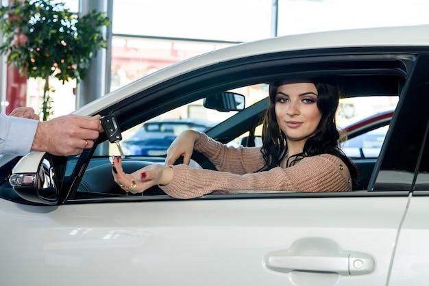 Mulher morena pegando as chaves do carro novo