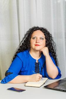 Mulher morena pensativa e encaracolada está sentada à mesa no escritório. foto vertical