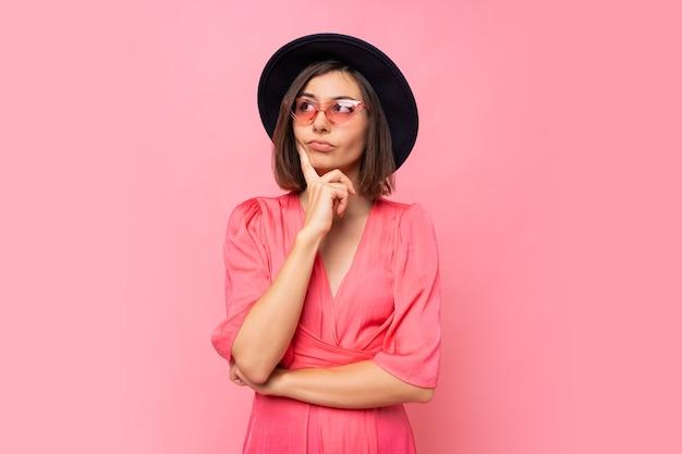 Mulher morena pensativa em óculos elegantes, posando sobre parede rosa.