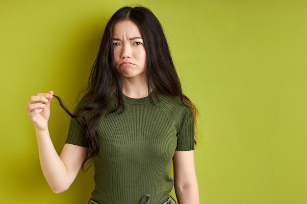 Mulher morena pensativa está olhando uma câmera enquanto segura uma mecha de cabelo nas mãos, precisa cortar, sentindo emoções tristes, fundo verde isolado