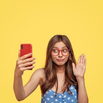 Mulher morena perplexa cumprimentando amigo durante a videochamada, acenando com a palma da mão para a câmera, segurando um celular moderno na frente do rosto
