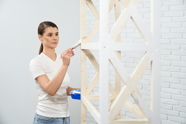 Mulher morena pintando prateleira de madeira em quarto vazio