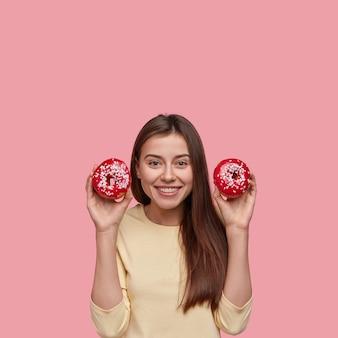 Mulher morena positiva carregando dois donuts nas mãos, sorrindo amplamente