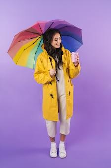 Mulher morena positiva em capa de chuva amarela posando isolado sobre a parede roxa segurando guarda-chuva e café.