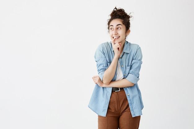 Mulher morena positiva emocional com coque de cabelo sorrindo amplamente, mantendo o dedo nos dentes, olhando de lado, pensando em algo bom. menina animada em camisa jeans posa contra parede branca