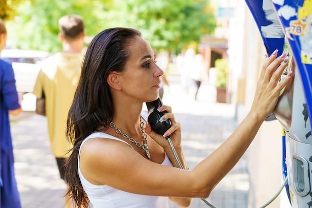 Mulher morena positiva segurando chamadas do receptor de telefone do papel de carta na rua, turista falando no telefone público trabalhando com moedas, feliz com a comunicação internacional em um dia ensolarado de verão