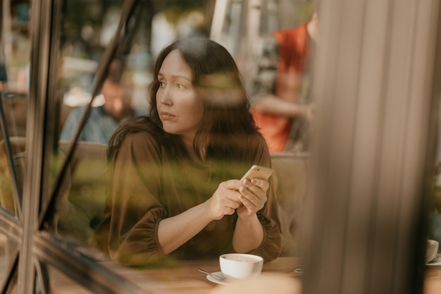Mulher morena preocupada, com longos cabelos cacheados, sentado à janela no café com o celular nas mãos