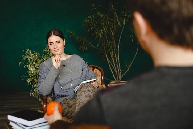 Mulher morena psicóloga de aparência europeia realiza consulta de paciente em seu consultório