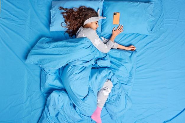 Mulher morena relaxada vestida de pijama coberto com edredom macio e quente tem sono profundo em poses de quarto na cama, o telefone móvel encontra-se perto de algum tempo antes do despertador. sesta tranquila