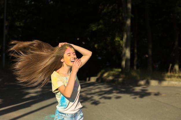 Mulher morena rindo com vento no cabelo brincando com tinta seca holi