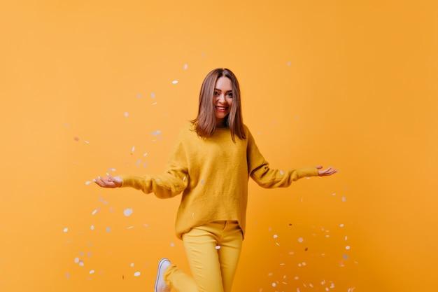 Mulher morena rindo em calças amarelas, expressando felicidade e jogando confetes fora. foto interna de cativante garota bem vestida dançando na parede brilhante.