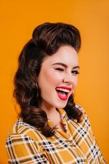 Mulher morena rindo posando em fundo amarelo. retrato de uma garota pin-up sorridente com camisa quadriculada.