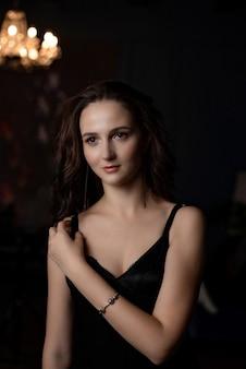 Mulher morena romântica com vestido de seda preta posando em um quarto escuro com um lustre
