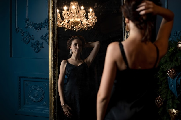 Mulher morena romântica de vestido preto se preparando e olhando para o espelho vintage