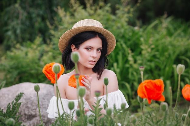 Mulher morena romântica no chapéu de palha com flor na mão, sentado no incrível campo de papoulas.