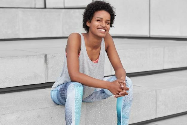 Mulher morena satisfeita com corte de cabelo afro, veste roupa esportiva, mantém as mãos juntas, tem expressão alegre, senta-se na escada, sente-se revigorada, cheia de energia após o treinamento cardiovascular. conceito de esporte