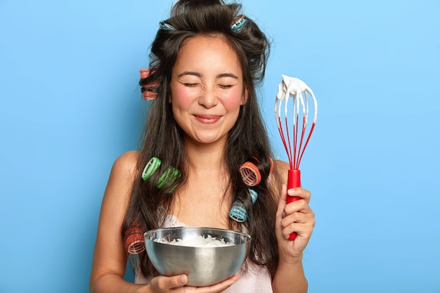 Mulher morena satisfeita com creme de leite azedo em uma tigela e usando rolos de cabelo